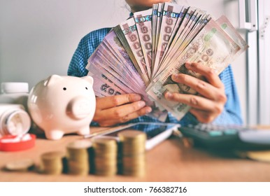Woman in blue shirt hold pile of money, white piggy bank, pills pouring from medicine bottle, mobile phone, calculator and blur rolls ladder of coins on wood table