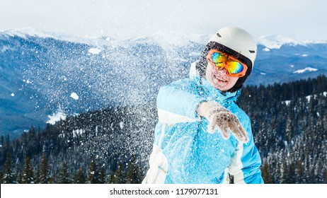 a woman in a blue ski suit and mask hurls snow at the camera on top of the mountain.the girl throws snow at the camera