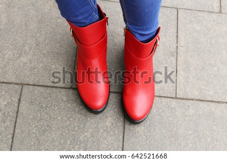 849265a79b0b Woman in blue skinny jeans walking on the city street. Girl in bright red  leather