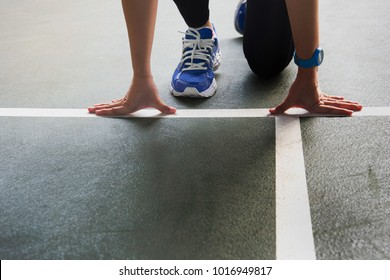 woman in blue sport shoes at start white line ready to running on dark green gym floor