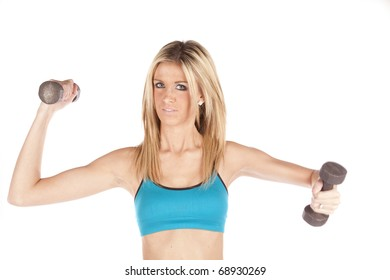 A woman in a blue sports bra is holding up some weights.