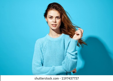 woman in blue sweater touches hair on her head