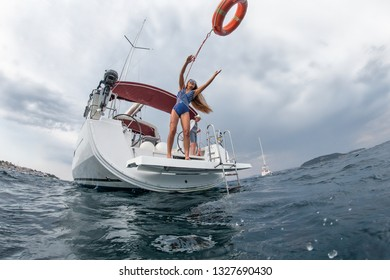 Woman in a blue swimming suit throwing orange lifebuoy on the yacht preparing for a safety