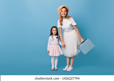 Woman in boater and white dress holds suitcase and poses with her daughter against blue background