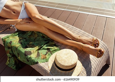Woman Body In Bikini. Female Long Legs With Hairless Smooth Sun Tan Skin Sunbathing On Lounge Chair At Swimming Pool. Beautiful Sexy Girl With Healthy Fit Body, Sexy Depilated Legs Relaxing In Summer