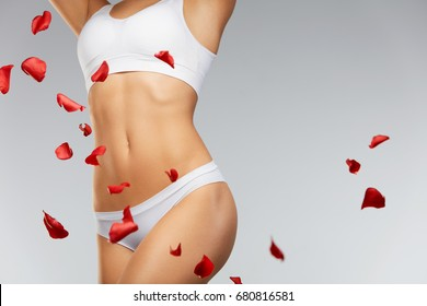 Woman Body Care. Beautiful Female Body In Shape With Fit Slim Figure, Smooth Soft Skin In Bikini Panties With Flying White And Red Rose Flower Petals. Closeup Girl's Body In Underwear. High Resolution