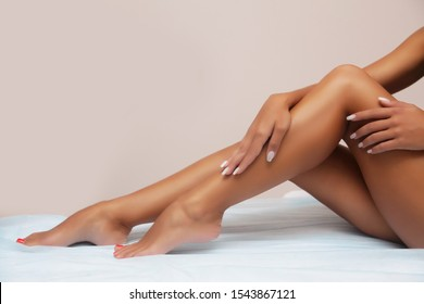 Woman body care. Close up of long female tanned legs with perfect smooth soft skin, pedicure, healthy nails on white background. Epilation, beauty and health concept
