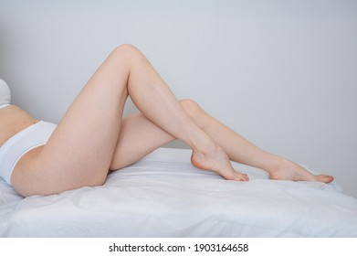 Woman body care. Close up of long female tanned legs with perfect smooth soft skin, pedicure, healthy nails on white medical couch and background. Epilation, beauty and health concept