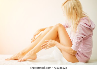 Woman Body Care. Close Up Of Long Female Legs With Perfect Smooth Soft Skin, Pedicure And Beautiful Hands With Natural Manicure, Healthy Nails On White Bed. Epilation, Beauty And Health Concepts