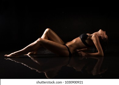 Woman Body Care. Sexy Perfect Female Body, Black Lingerie in the Aqua Studio Background And Water Reflection With Smooth Soft Skin. Epilation, Liposuction Cosmetology. Professional Spraying Tan.