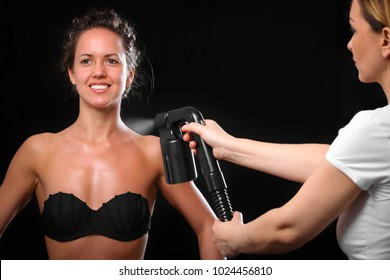 Woman body paint with airbrush in professional beauty salon