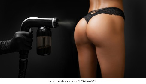 Woman body paint with airbrush spray tan in professional beauty salon on black background.