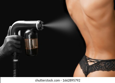 Woman body paint instant tan spray skintone with airbrush in professional beauty salon on black background.