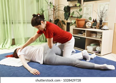 Woman body twist during yumeiho massage. This oriental therapy is a complex set of manual procedures and physical exercises. Horizontal shot