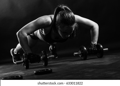 Woman bodybuilder lifting dumbbell isolated over black background, Black and white.