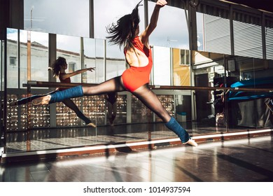 Woman in bodysuit and pointe shoes jumping above ground in studio with hair flying.