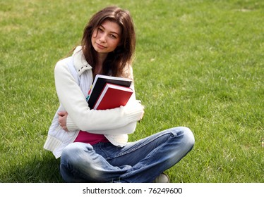 Woman with book in green grass on summer park