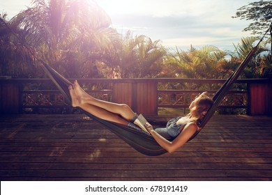 woman with book in her hands is resting in a hammock on the terrace against the background of a sunset in the jungle during a vacation.