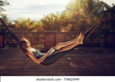woman with book in her hands is resting in hammock on the terrace against the background of sunset in the jungle during a vacation.