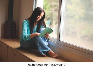 woman with a book sitting on the window sill