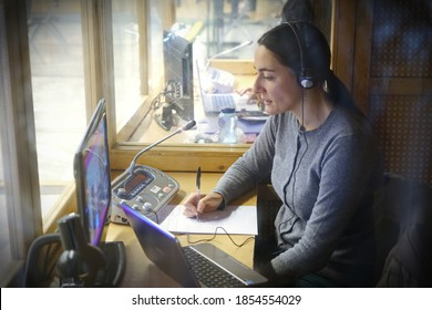 A woman in the booth for simultaneous translation during a remote online event. Turin, Italy - november 2020
