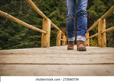 Woman in boots and blue jeans walks on wooden bridge in park