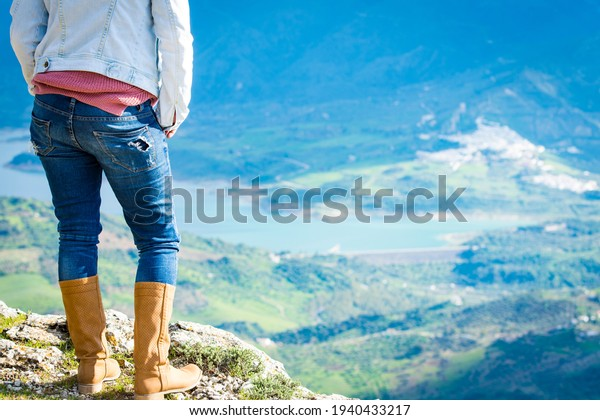 woman with boots and jeans, observing the landscape in the mountain