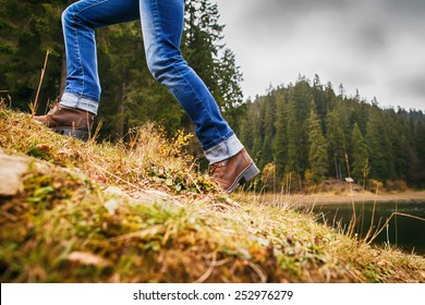 Woman in boots and jeans walking up on hill in forest