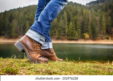 Woman in boots and jeans walks along the lake shore in autumn forest