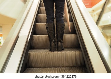 woman with boots and pink umbrella on escalator