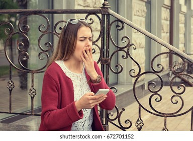 Woman bored and yawning watching media in a mobile phone sitting outdoors outside near her home in Manhattan New York
