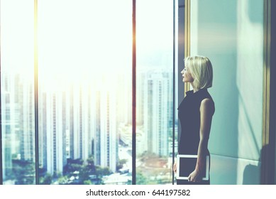 Woman boss with digital tablet in hand is watching in office window with copy space for content, while is resting after conference with her staff. Female manager is thinking about future work plan