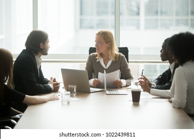 Woman boss discussing new project or financial report at group briefing with diverse employees, serious focused female executive planning work with team at corporate meeting, multiracial teamwork