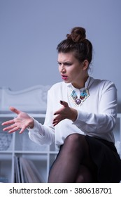 Woman boss, elegant and attractive sitting, gesticulating with grimace on face
