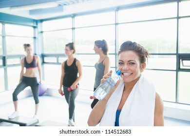 Woman with bottle of water in aerobics class in gym
