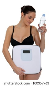 Woman with bottle of water and scales