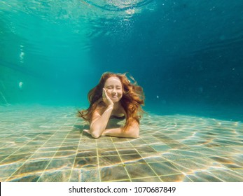 Woman at the bottom of the pool, she dives under the water