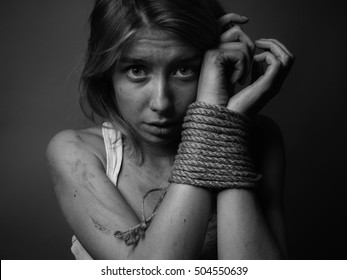Woman with bound hands on gray background. Black and white