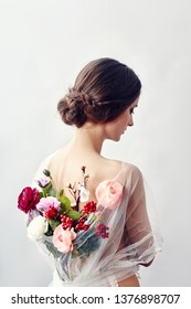 Woman with a bouquet of artificial flowers behind her. The girl in a light transparent dress with an open back and flowers. Art portrait of a woman for the cover of the book