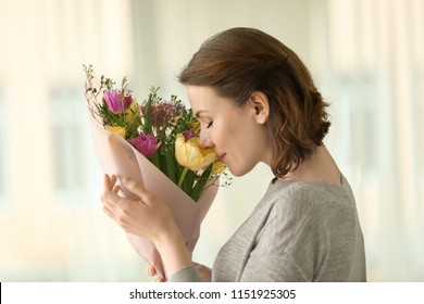 Woman with bouquet of beautiful flowers at home