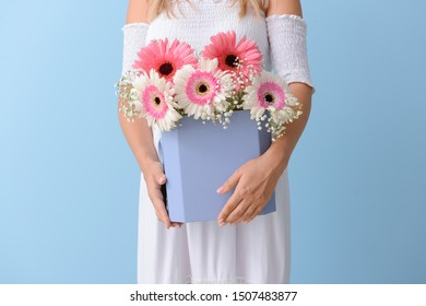 Woman with bouquet of beautiful gerbera flowers on color background