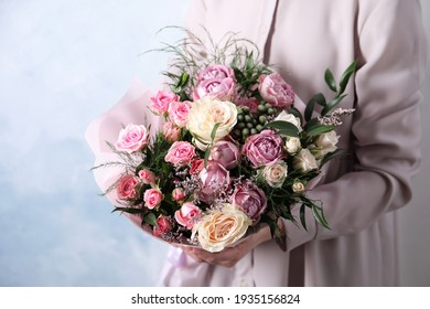 Woman with bouquet of beautiful roses on light blue background, closeup