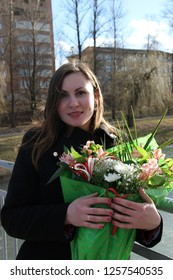 Woman with a bouquet of flowers on the bridge on the background of the lake on the day of holy valentine