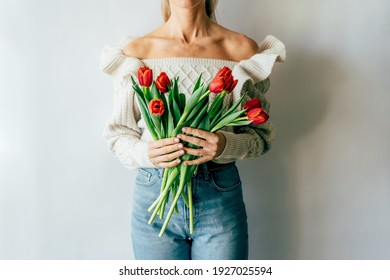Woman with bouquet of fresh spring blooming tulips.