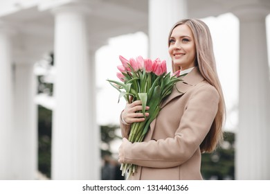 woman with bouquet of tupils in spring. outdoor portrait of young smiling girl with flowers in the street