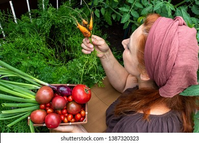 Woman with a bowl full of tomatoes from her garden