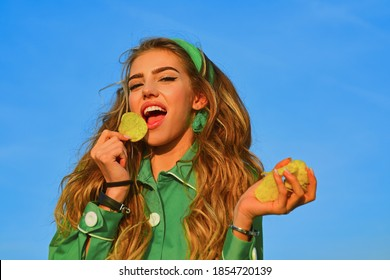 Woman with bowl of potato chips on blue background. Young attractive girl biting with hunger one piece of chips. Sexy spicy potatoe chips