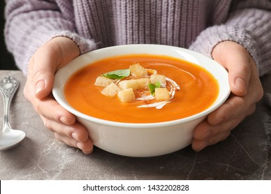 Woman with bowl of tasty sweet potato soup at table, closeup
