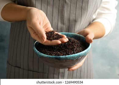 Woman with bowl of uncooked black rice, closeup