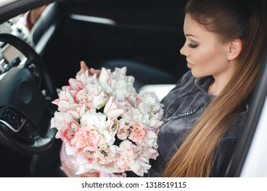 woman with box of flowers sitting in car. happy girl with flower bouquet for holiday